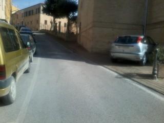 Un'automobile parcheggiata sul marciapiede della chiesa di Roncitelli