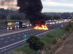 Un momento dell'assalto al portavalori sull'autostrada A14 tra Ancona e Loreto: due auto incendiate