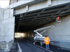 Operai predispongono illuminazione in un sottopasso