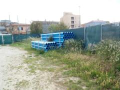 Parcheggio ex Italcementi dissestato con erba alta buche e deposito attrezzi