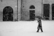 Un passante sotto la neve al Foro