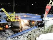 Operai staccano la struttura del ponte con la fiamma ossidrica